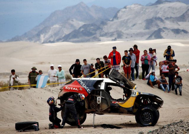 Carlos Sainz (L) of Spain and co-pilot Lucas Cruz work on a tire of their Peugeot during the 10th stage of the Dakar Rally 2016 near Fiambala, Argentina, January 13, 2016. (Photo by Marcos Brindicci/Reuters)