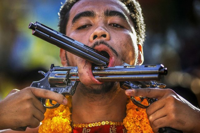 A devotee is pierced with two pistols. (Photo by Athit Perawongmetha/Reuters)