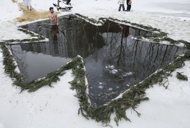 A man crosses himself as he takes a dip in a lake during Orthodox Epiphany celebrations in Kiev, Ukraine, January 19, 2016. (Photo by Gleb Garanich/Reuters)
