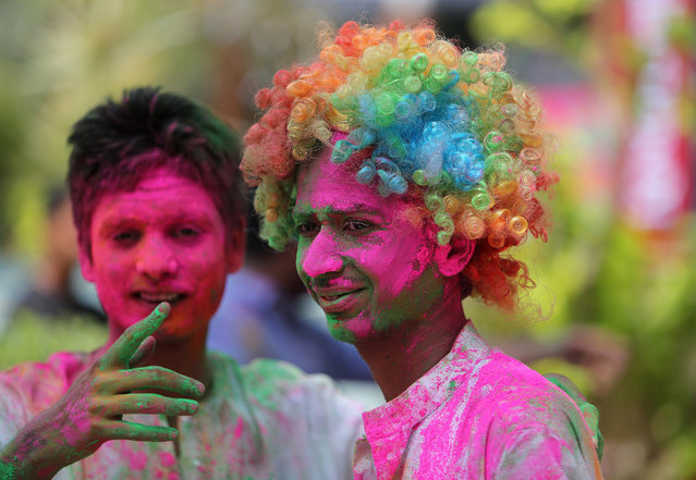 Indians stand with their faces smeared with coloured powder during Holi celebrations in Hyderabad, India, Friday, March 6, 2015. Holi, the Hindu festival of colors, also marks the advent of spring. (AP Photo/Mahesh Kumar A.)