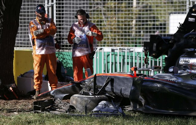 Course officials stand next to the car of McLaren Formula One driver Kevin Magnussen of Denmark after he crashed during the second practice session of the Australian F1 Grand Prix at the Albert Park circuit in Melbourne March 13, 2015. REUTERS/Jason Reed