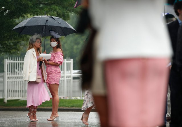 Racegoers shelter from the rain under umbrellas on the first day of the Epsom Derby Festival horse racing event in Surrey, southern England on June 4, 2021. (Photo by Peter Cziborra/Action Images via Reuters)