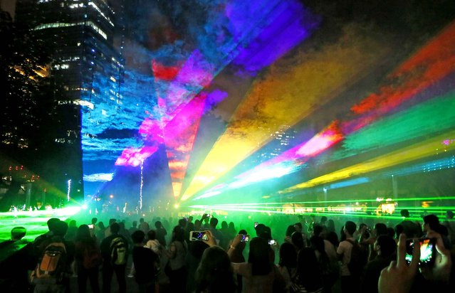 """People watch the """"Christmas and Light"""" show Friday, December 16, 2016, at the financial district of Makati city east of Manila, Philippines. The """"dancing"""" lights and laser show, which boasts of over a million Christmas lights, has attracted thousands of Filipinos every Yuletide season. (Photo by Bullit Marquez/AP Photo)"""