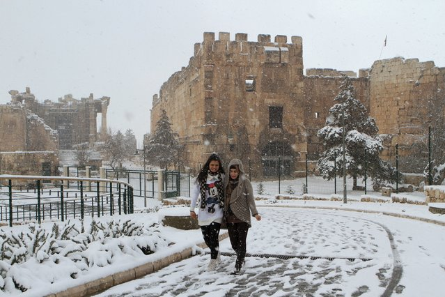 Women walk in snow at the historical ruins of Baalbek in eastern Lebanon, January 25, 2016. (Photo by Ahmed Shalha/Reuters)