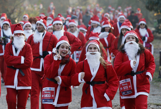 People dressed in Santa Claus costumes take part in a run in Milan, Italy, Saturday, December 17, 2016. (Photo by Antonio Calanni/AP Photo)