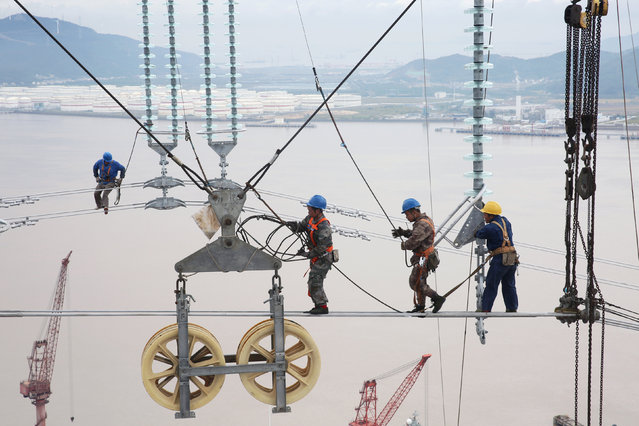 Men work on cables connecting power transmission towers in Zhoushan, Zhejiang province, China October 22, 2018. (Photo by Reuters/China Stringer Network)