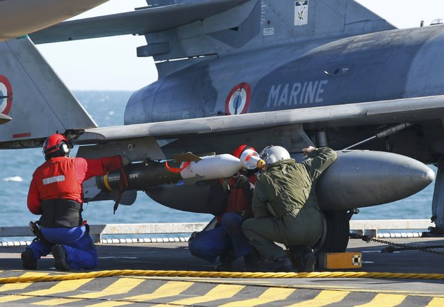 A pilot (R) and crew check ordnance under a Super Etendard fighter jet aboard France's Charles de Gaulle aircraft carrier which continues its mission in the Gulf, January 28, 2016. (Photo by Philippe Wojazer/Reuters)