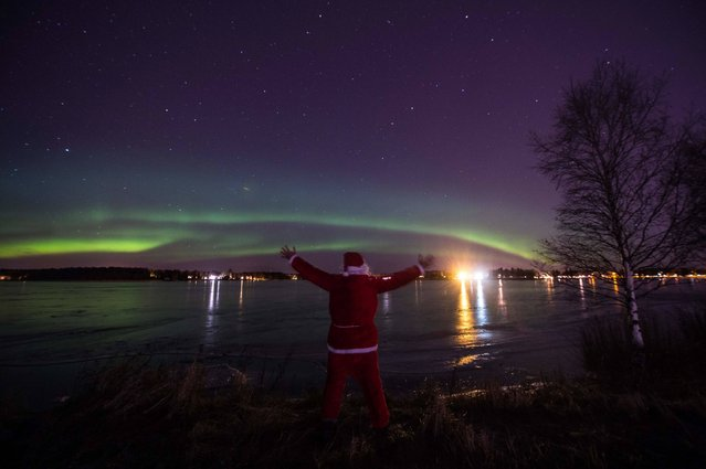 A man dressed as Santa Claus looks at northern lights in Vaasa by 63°N, on December 23, 2016. (Photo by Olivier Morin/AFP Photo)