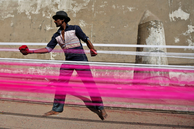A worker applies colour to strings which will be used to fly kites, on a roadside in Ahmedabad, India, December 15, 2016. (Photo by Amit Dave/Reuters)