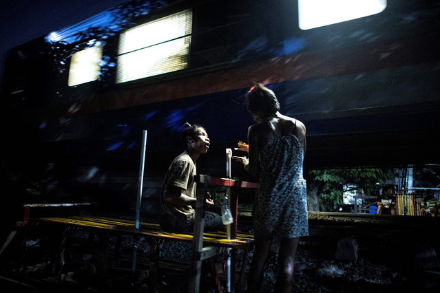 """This picture taken on October 19, 2018 shows """"trolley boy"""" couple Tyson Aguha (L) and Joan Acebo (R) chatting along a train track as a train passes by in Manila, Philippines. (Photo by Noel Celis/AFP Photo)"""