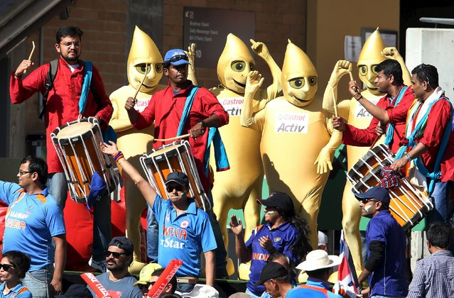 People dressed as oil drops promoting an oil company dance with drummers supporting India's cricket team during the Cricket World Cup semi-final match against Australia in Sydney, March 26, 2015. (Photo by Steve Christo/Reuters)