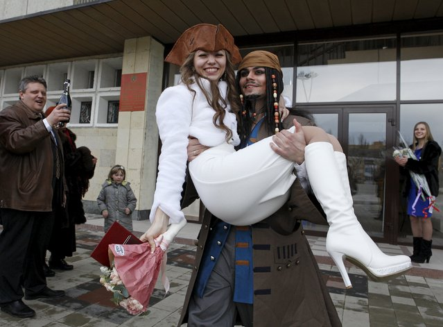 German Yesakov, 25, a cameraman from Russia, dressed as movie character Captain Jack Sparrow, carries his bride Anastasiya in his arms during their wedding ceremony near a registry office in the southern city of Stavropol, Russia, February 5, 2016. (Photo by Eduard Korniyenko/Reuters)