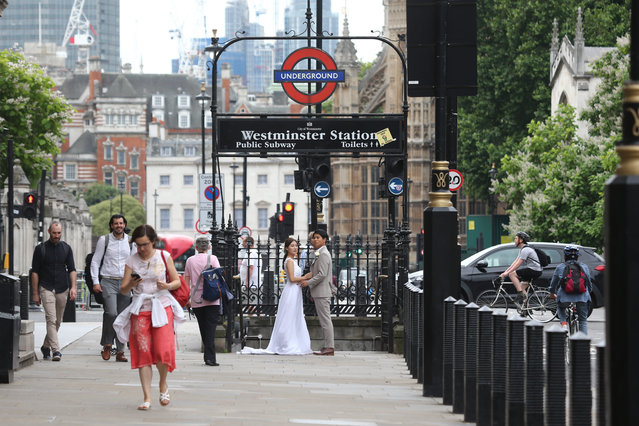 An East Asian couple pose for their wedding photographers outside Westminster Station in London as people pass by on July 15, 2021. In the UK from 19 July, there will be no limits on the number of people who can attend services or receptions, whatever the venue is. Current social distancing and face covering rules will no longer apply, there will be no requirement for table service, and restrictions around singing and dancing will also end. (Photo by Tayfun Salci/ZUMA Wire/Rex Features/Shutterstock)