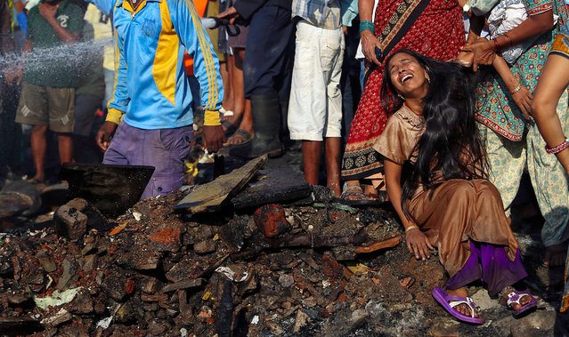 An Indian woman cries while her baby is missing after a fire in Ambedkar Nagar slum in Mumbai, India, 21 November 2013. According to reports, a fire broke out in the area on 21 November, gutting shanties, but no casualties have been reported. (Photo by Divyakant Solanki/EPA)