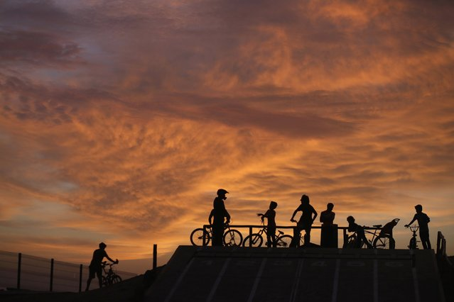Cyclists wait to perform stunts during sunset at a park in Lima's Miraflores district, February 23, 2015. (Photo by Mariana Bazo/Reuters)