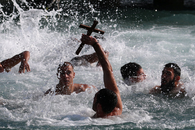 A man holds a cross during a competition to retrieve it from the water during Epiphany day celebrations in the port village of Zygi, near Limassol, Cyprus, January 6, 2018. (Photo by Yiannis Kourtoglou/Reuters)