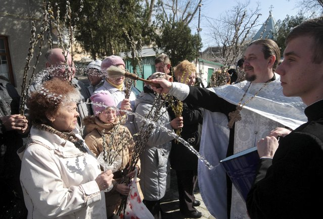 A priest sprinkles believers with holy water during the celebrations for Palm Sunday in the Crimean port of Yevpatoriya April 5, 2015. Palm Sunday commemorates Christ's triumphant entry into Jerusalem. The symbol of the religious feast in Russia is willow instead palm because of the climate particularity. (Photo by Pavel Rebrov/Reuters)