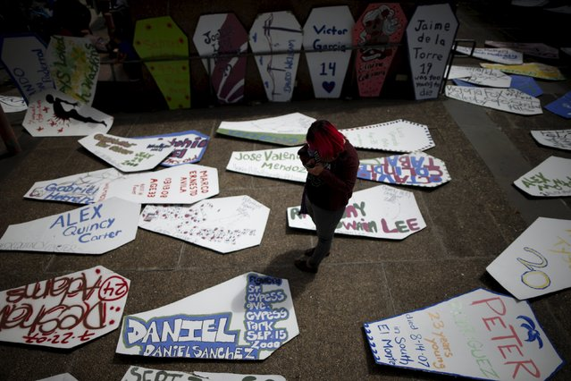 A woman walks through a field of cardboard coffins to commemorate the more than 617 people march organizers say have been killed by law enforcement in LA County since 2000, in Los Angeles, California April 7, 2015. (Photo by Lucy Nicholson/Reuters)