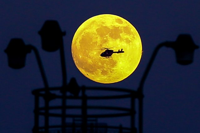 A helicopter flies in front of the Wolf Moon as it rises over London, England on January 20, 2019. The Wolf Moon, the Full Moon on January 20-21, 2019, is a Supermoon, making it look bigger and brighter than usual during the total lunar eclipse. (Photo by Dinendra Haria/Rex Features/Shutterstock)