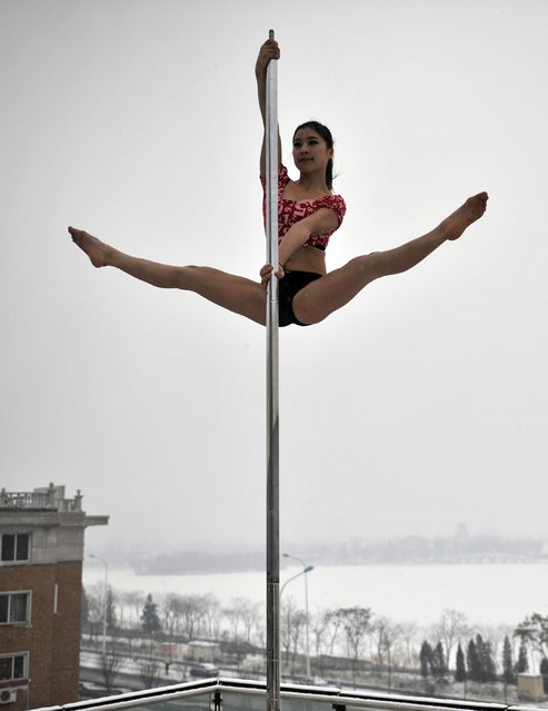 This picture taken on December 17, 2013 shows a pole dancer practising after it snowed in Tianjin during a promotional event by members of China's national pole dancing team and students of the sport. (Photo by AFP Photo)