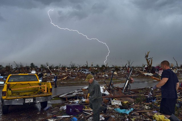 Lightning strikes during a thunder storm as tornado survivors search for salvagable stuffs at their devastated home on May 23, 2013, in Moore, Oklahoma. (Photo by Jewel Samad/AFP Photo)