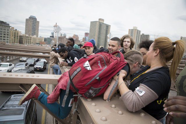 Demonstrators climb on the Brooklyn Bridge during a protest against police brutality against minorities, in New York April 14, 2015. (Photo by Brendan McDermid/Reuters)