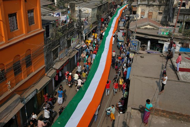 People carry an Indian national flag which according to organisers measures 1100 metres (3609 feet) through a street during Republic Day celebrations on the outskirts of Kolkata, January 26, 2019. (Photo by Rupak De Chowdhuri/Reuters)