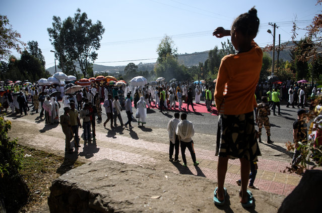 A girl looks on as worshippers and Ethiopian Orthodox priests carrying Tabots take part in a procession to mark the annual Timkat epiphany celebration on January 18, 2017 in Gondar, Ethiopia. (Photo by Carl Court/Getty Images)