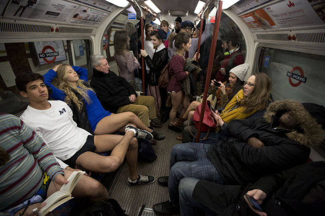 """People take part in the """"No Trousers Tube Ride"""" event next to other passengers on an underground train in London, Sunday, January 12, 2014. The stunt was held to coincide with the """"Global No Pants Subway Ride"""", where passengers board subway cars in the middle of winter without wearing trousers and act normally. (Photo by Matt Dunham/AP Photo)"""