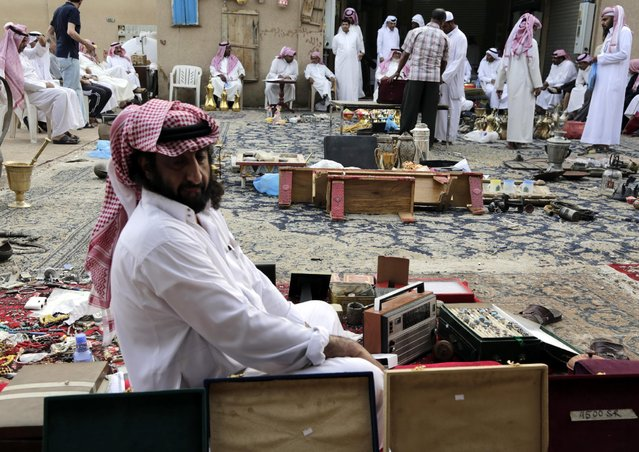In this April 16, 2015 photo, a Saudi vendor sits amid his goods at al-Aqeeliya open-air auction market in Riyadh, Saudi Arabia. At an auction in an empty quarter of the market, dozens of men drink tea, smoke cigarettes and yell out prices over one another in bids for handmade Arabian swords, old mobile phones, wooden chests, copper and gold-colored tea kettles, and even a stuffed hawk. (Photo by Hasan Jamali/AP Photo)