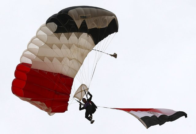 An Egyptian paratrooper with a parachute in the colours of the national flag, lands during the opening of the Egyptian International Parachuting Championship, which is organized by Egyptian Parachuting and Air Sports Federation (EPAF), in Giza, Egypt March 2, 2016. (Photo by Amr Abdallah Dalsh/Reuters)