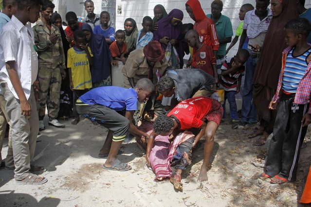 Somalis carry a civilian  body who was killed  in a car bomb which was exploded outside a restaurant  in Mogadishu, Somalia, Tuesday, April ,21 , 2015. A car bomb killed  people and injured several others at a restaurant in Somalia's capital on Tuesday, police said. Security forces have secured the area around the Banoda restaurant in Mogadishu, said senior police officer Mohamed Abdi. The car with the bomb was parked near Somalia's presidential palace, he said. (Photo by Farah Abdi Warsameh/AP Photo)