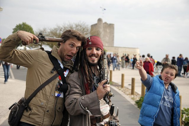 Julien Godard, dressed as Captain Sparrow, right, poses for souvenir picture prior to the departure of the replica of the frigate Hermione, used to bring French troops and funds to American revolutionaries in 1780, in Fouras, southwest France, on his way for its transatlantic voyage, Saturday, April 18, 2015. (Photo by Francois Mori/AP Photo)