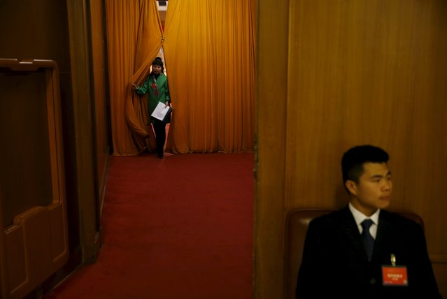 A woman walks out as a security officer sits on guard during the opening session of the National People's Congress (NPC) at the Great Hall of the People, in Beijing, China, March 5, 2016. (Photo by Damir Sagolj/Reuters)