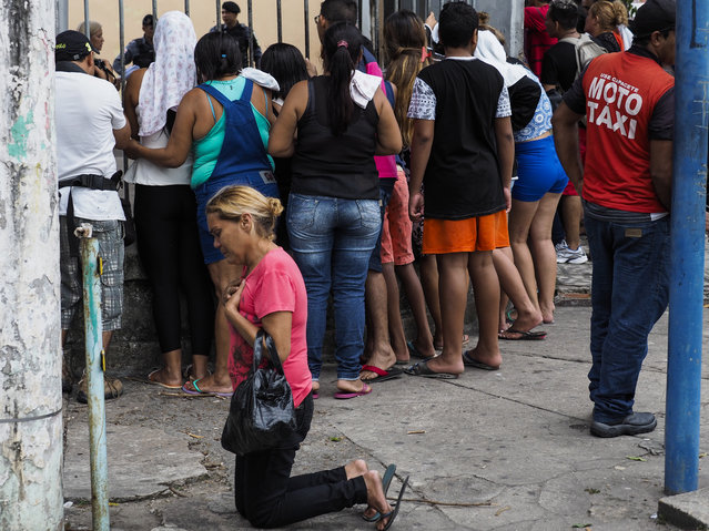 A relative of an inmate of the Desembargador Raimundo Vidal Pessoa Public Jail kneels to give thanks after finding out her loved one is not among those killed during a riot on January 8, 2017 in Manaus, Amazonas state, Brazil. At least four inmates were killed in a facility in Manaus, the capital of Amazonas state, sending the number of violent prison fatalities to over 100 in just one week. Deadly prison riots have intensified in Brazil since a truce broke down in July between the country' s two largest drug gangs, the First Capital Command (PCC) and the Red Command (CV). (Photo by Raphael Alves/AFP Photo)
