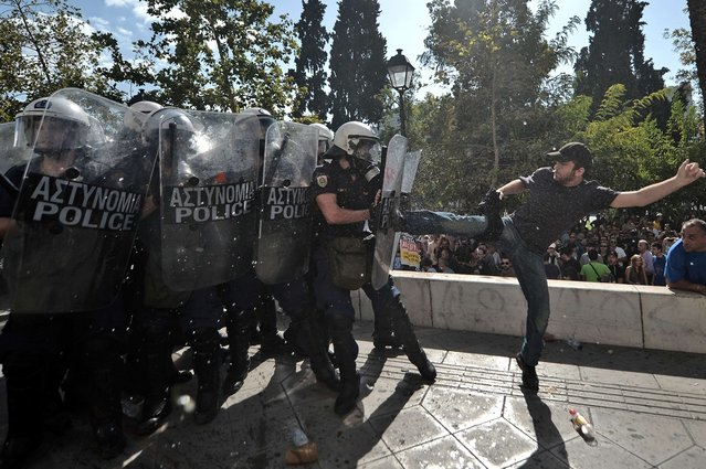 A demonstrator clashes with riot police during a 24-hour strike in Athens on October 18, 2012. (Photo by Aris Messinis/AFP Photo)