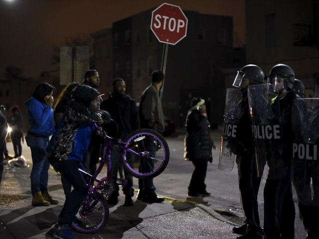 A demonstrator holds up a bicycle as he faces law enforcement officers standing guard near Baltimore Police Department Western District during a protest against the death in police custody of Freddie Gray in Baltimore April 25, 2015. (Photo by Sait Serkan Gurbuz/Reuters)