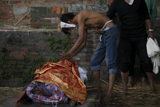 A boy cries over the body of his father at a cremation ground after an earthquake in Bhaktapur, Nepal April 27, 2015. (Photo by Adnan Abidi/Reuters)