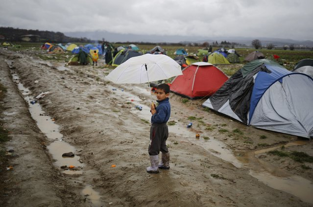 A migrant boy holds his umbrella while standing in a mud at a makeshift camp on the Greek-Macedonian border, near the village of Idomeni, Greece March 10, 2016. (Photo by Stoyan Nenov/Reuters)