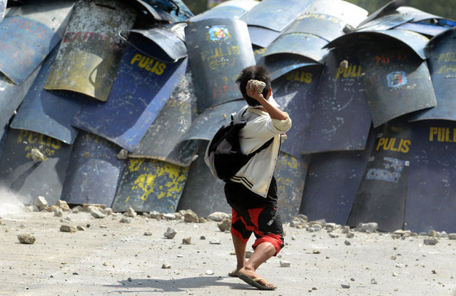A residents throws a stone and at policemen during a demolition operation in a squatters area in Manila on January 27, 2014. The government wants to redevelop the area into a business district in a joint venture with a private firm. (Photo by Noel Celis/AFP Photo)