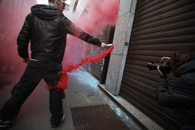 A man hold a smoke flare during a protest against Expo 2015 in Milan, Italy, Thursday, April 30, 2015. (Photo by Luca Bruno/AP Photo)