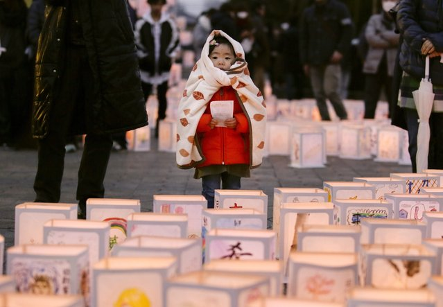 A little girl looks at candle lanterns, during a memorial ceremony for tsunami victims at the tsunami-devastated city of Natori, Miyagi Prefecture, Northern Japan, 11 March 2016. Japan marks the fifth anniversary of the earthquake and tsunami. Japan's National Police Agency announced that as of February 2016, 15,894 people were killed in the disaster, 2,562 are still missing, and some 174,471 people are still living in shelters. (Photo by Kimimasa Mayama/EPA)
