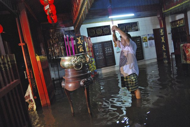 An Indonesian ethnic Chinese holds up incense sticks as he prays in a flooded temple during Lunar New Year celebration in Kudus, Central Java, Indonesia, Friday, January 31, 2014. Heavy tropical downpours often cause floodings each year in the country, where millions of people live in mountainous regions and near fertile flood plains close to rivers. (Photo by Andreas Fitri Atmoko/AP Photo)