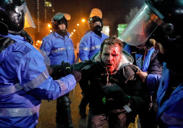 Romanian riot police detain a man, face covered in blood, after minor clashes erupted during a protest in Bucharest, Romania, Thursday, February 2, 2017. (Photo  by Vadim Ghirda/AP Photo)