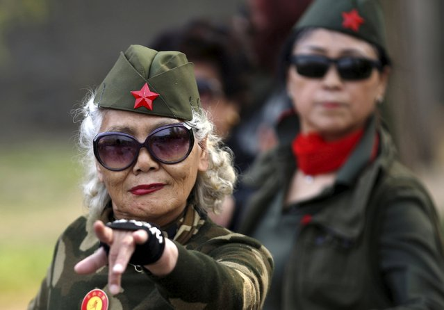 Seventy-nine-year-old Wang Baorong, dressed in military style clothes, performs square dancing at a park square in Beijing, China, April 9, 2015. (Photo by Kim Kyung-Hoon/Reuters)