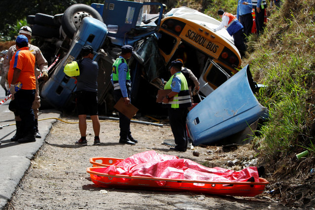 Rescue workers stand next to dead bodies after a crash between a bus and a truck on the outskirts of Tegucigalpa, Honduras, February 5, 2017. (Photo by Jorge Cabrera/Reuters)