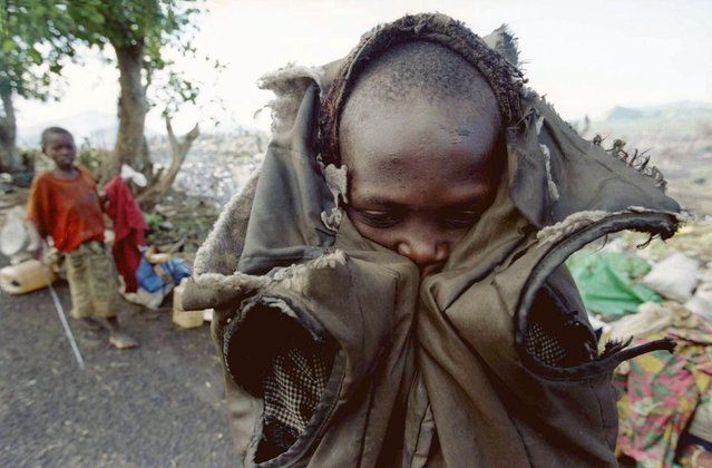 A little Rwandan refugee, who traveled from Bukavu in the former Zaire, shivers in the early morning hours before getting back on the road to the border, November 30, 1996. He was part of a group of some 20,000 refugees, many suffering from disease and malnutrition, who made their way into Goma in what is now the Democratic Republic of the Congo, after being on the road for over one month. (Photo by Corinne Dufka/Reuters)