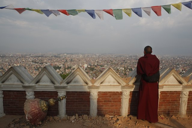 A Buddhist monk catches an aerial view of Kathmandu from the damaged Swayambhunath Stupa premises in Kathmandu, Nepal, Wednesday, May 6, 2015. The April 25 earthquake killed thousands and injured many more as it flattened mountain villages and destroyed buildings and archaeological sites in Kathmandu. (Photo by Niranjan Shrestha/AP Photo)