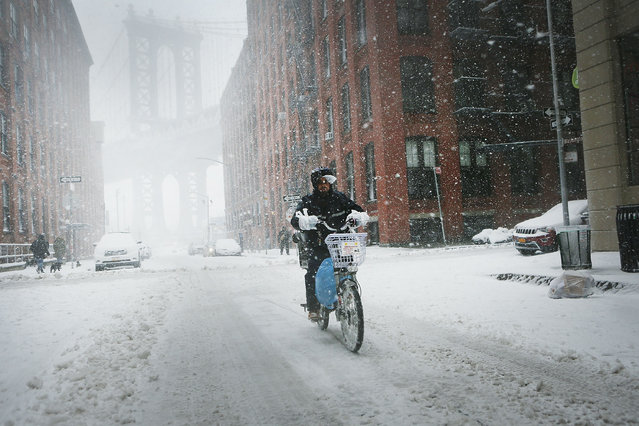A delivery man rides a bike through the snow and wind on February 9, 2017 in the Brooklyn borough of New York City. (Photo by Spencer Platt/Getty Images)