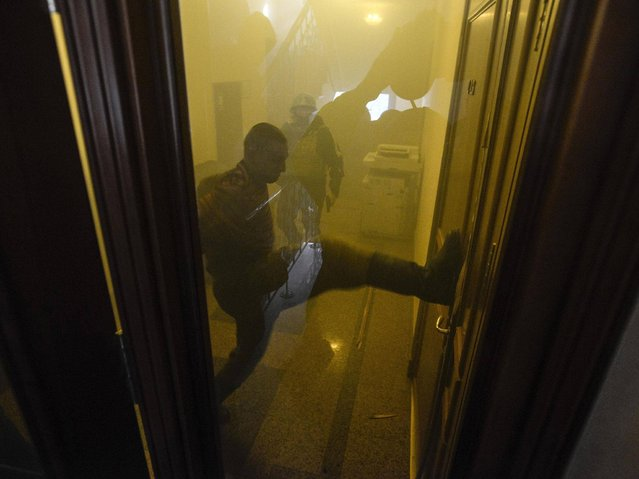"Anti-government protesters attempt to break a door inside an office of the pro-presidential ""Party of the Regions"" in Kiev. (Photo by Andrew Kravchenko/Reuters)"